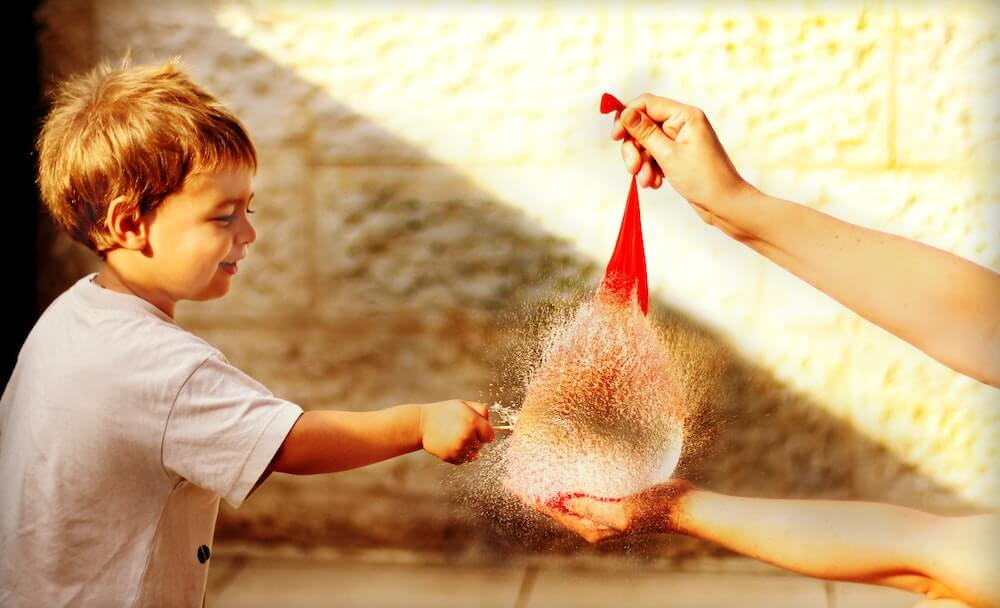 Child breaking water balloon